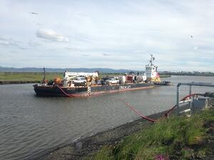 The Sesok and barge anchoring in the river at Unalakleet delivering their fuel