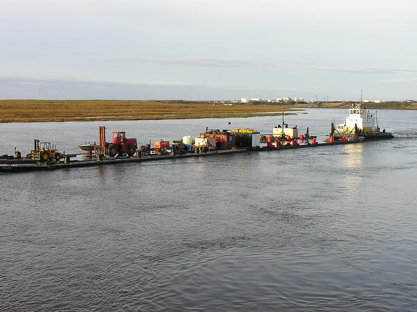The Toolik departing Bethel heading up river with their barges.